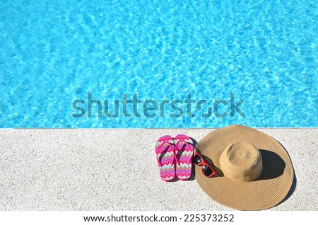 Sun hat with sunglasses and flip-flops beside the blue pool -- Summer vacations concept  - stock photo
