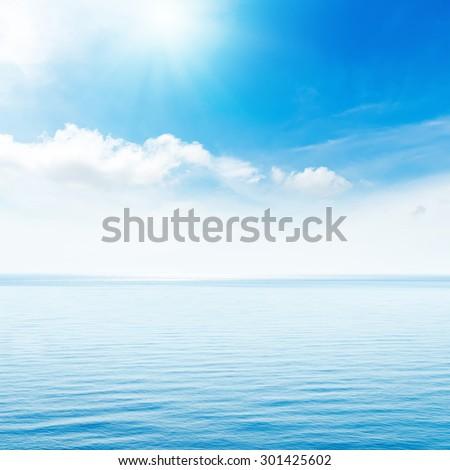 sun in blue clouds over sea - stock photo