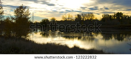 Sun is about to rise over a small wetland refuge on the Colorado prairie - stock photo