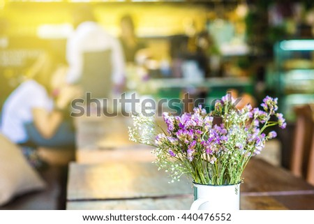 Sun light with vintage flowers on wooden in cafe background, Bouquet flower - stock photo