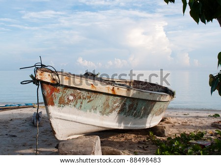 Sun lit boat on the beach - stock photo