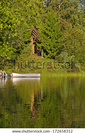 Sun lit cabin in the woods on the edge of a lake with a fishing boat moored in front. - stock photo