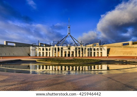 Sun lit facade of National Parliament house of Australia in Canberra in the morning. Columns of house entrance reflecting in fountain still waters. Public building with free access for public. - stock photo