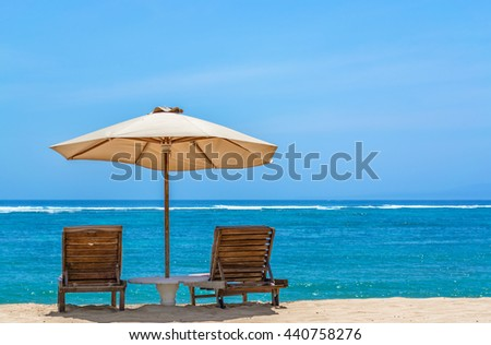 Sun lounger on beautiful tropical beach with a umbrella and small table.