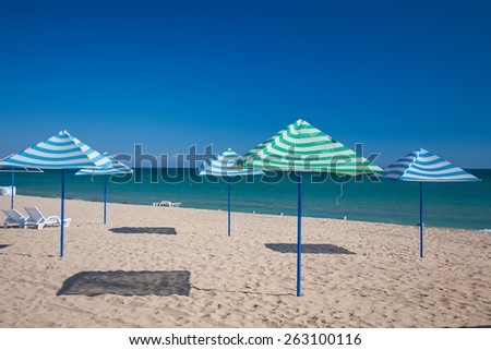 Sun loungers and straw shade umbrellas on a beach - stock photo