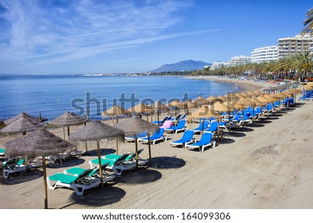 Sun loungers and straw shade umbrellas on a beach by the Mediterranean Sea in Marbella, Costa del Sol, Spain. - stock photo