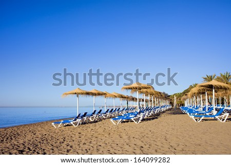 Sun loungers on a tranquil beach at the popular resort city of Marbella in Spain, Costa del Sol, Malaga province. - stock photo