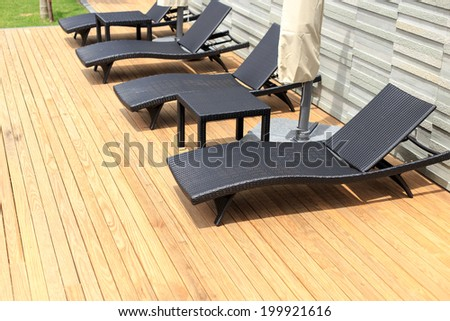 sun loungers stand on decking at pool - stock photo