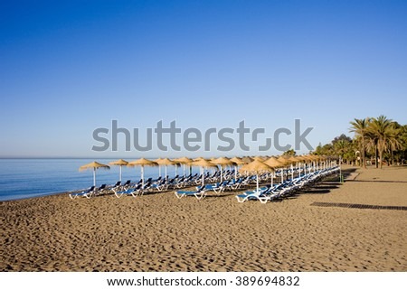 Sun loungers with umbrellas on a beach, sunny morning in resort city of Marbella, Costa del Sol, Spain - stock photo