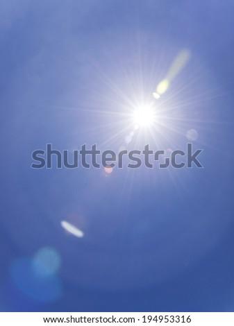 Sun on blue sky with lenses flare.  - stock photo
