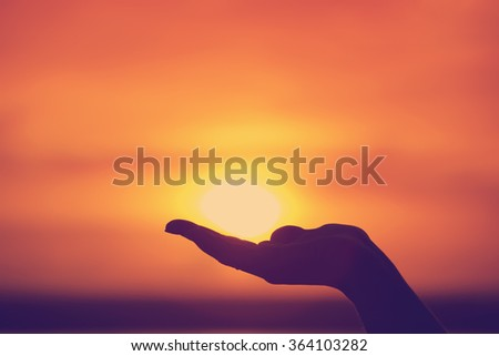 Sun on female hand. Silhouette of hand holding sun  - stock photo