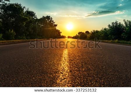 sun over asphalt road - stock photo