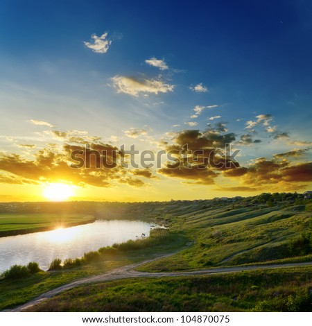 sun over river with dramatic sky