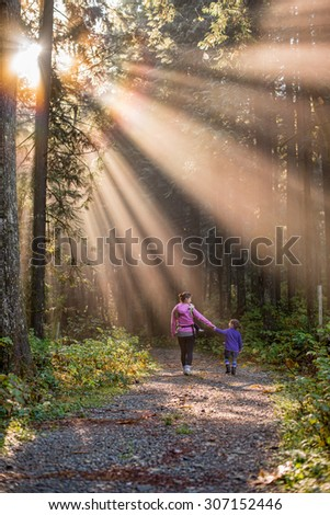 Sun rays beating down on mother and daughter walking in forest - stock photo