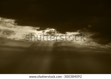 Sun rays glowing through the clouds. Dramatic lighting before a storm. Apocalypse concept. Aged photo. Sepia. - stock photo