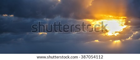 sun rays  in a grey sky at sunset - stock photo
