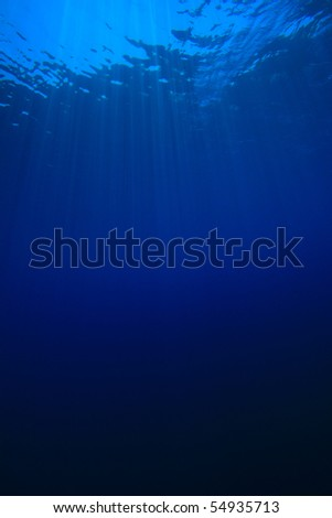 Sun rays in blue water - stock photo