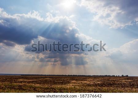 Sun rays of the setting sun over the arable land  - stock photo