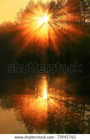Sun rays pass through the mist on the lake - stock photo