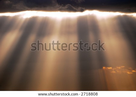 Sun rays shining through the clouds - stock photo