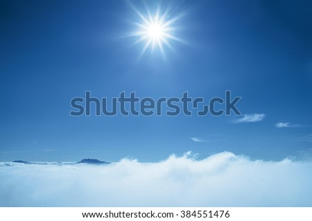 Sun rays shinning in the blue sky. Blue sky with layer of white hazy clouds. - stock photo