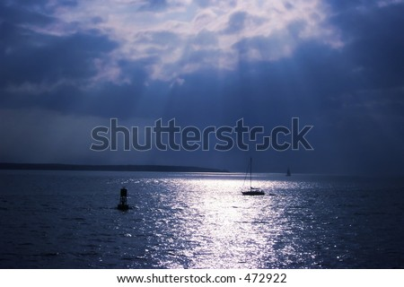 Sun rays streaking through the clouds over water