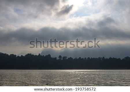 Sun rays streaming down onto the lake with mountain background