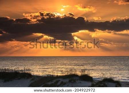 Sun rays stretch outward and upward from behind a dark cloud to light and paint the sky above the Atlantic Ocean on the Eastern coast of the Outer Banks in North Carolina at sunrise. - stock photo