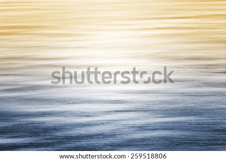 Sun reflecting off of the Pacific ocean with a blue to yellow gradient.  Image made with panning motion and a long exposure for a smooth, soft focus effect. - stock photo