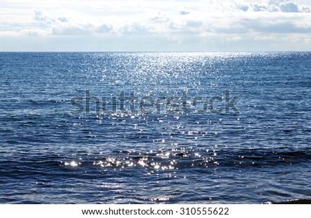 Sun reflecting on sparkling blue sea - stock photo
