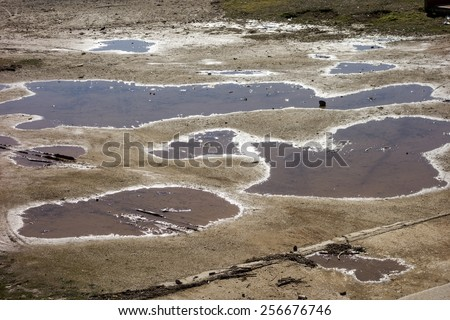Sun reflection in water puddles - stock photo