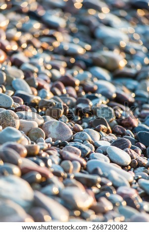 sun reflections on Stones on the beach and sea water in sunset light - stock photo