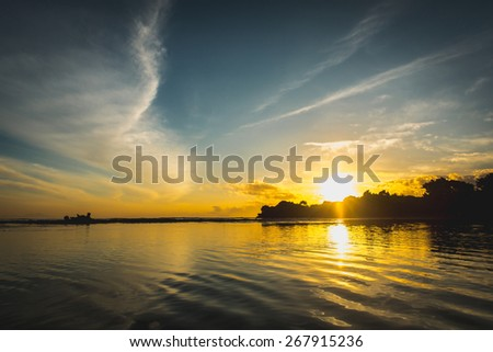 Sun rise from the trees and reflect together with clouds and sky in the water surface. Striking sunset above the ocean bay with bright clouds and sky. - stock photo