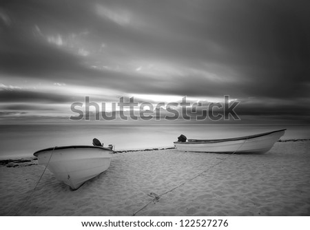 Sun rise on the beach with boats  Black and White - stock photo