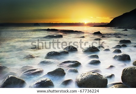 Sun Rise over the sea by the mountain - stock photo