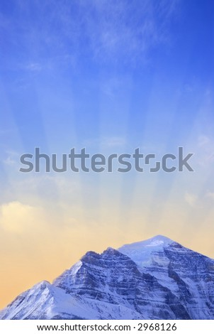 Sun rising behind a big snowy mountain - background with sun rays - stock photo