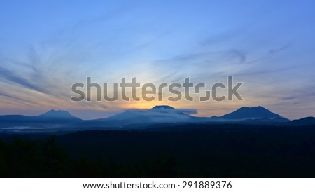 Sun rising behind the mountains in East Java, Indonesia - stock photo