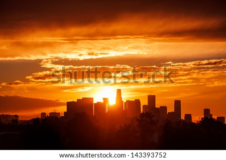 Sun rising over Los Angeles city skyline - stock photo