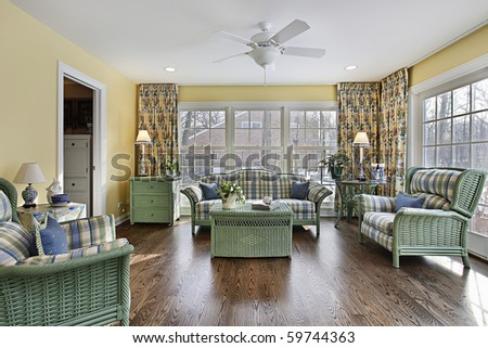 Sun room in suburban home with green wicker furniture - stock photo