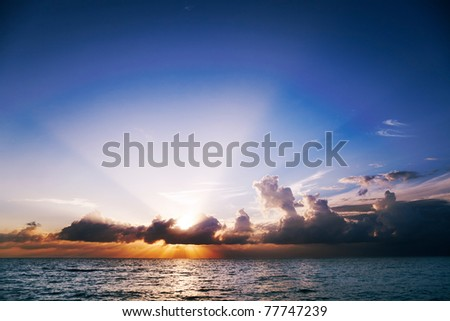 Sun's rays fan out from clouds at sunset over Seven Mile Beach, Grand Cayman - stock photo