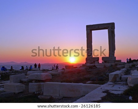 sun set behind the naxos arch in greece
