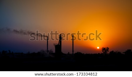 Sun set in industrial area  ,Industrial pollution, dangerous toxic smoke coming out from the chimney