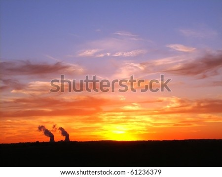 Sun sets over two cooling towers at a nuclear plant - stock photo