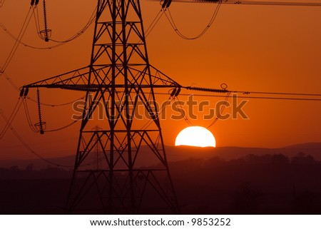 Sun setting behind a silhouetted electricity pylons - stock photo