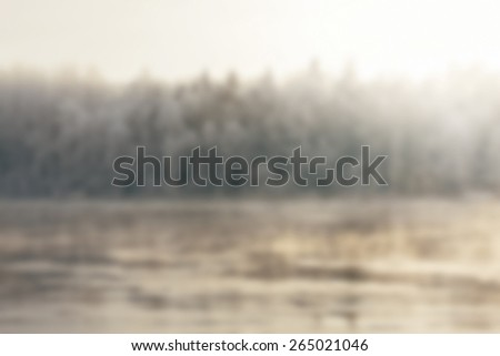 Sun Setting Behind Freezing Frosty Winter River in Blurry Background Image - stock photo