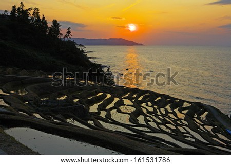 Sun setting over an ocean and beach. - stock photo