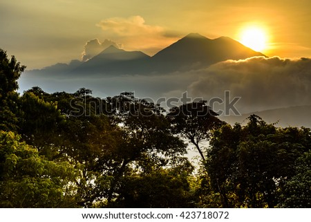 Sun setting over Fuego volcano & Acatenango volcano near Spanish colonial town & UNESCO World Heritage Site of Antigua, Guatemala, Central America - stock photo