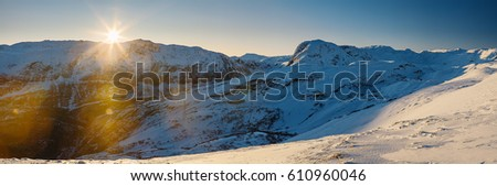 Sun setting over mountain range covered with snow. Norway.
