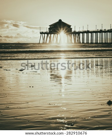 Sun Setting under the Huntington Beach Pier in Southern California with sunburst and reflection in the wet sand with a vintage retro filter in toned black and white. - stock photo