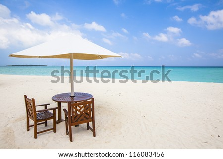 sun shade with two chairs at the beach - stock photo